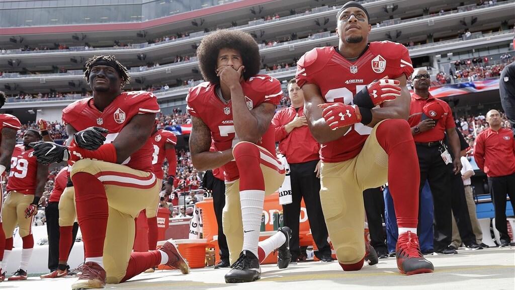 Colin Kaepernick en twee andere American footballspelers knielen tijdens volkslied in 2016.