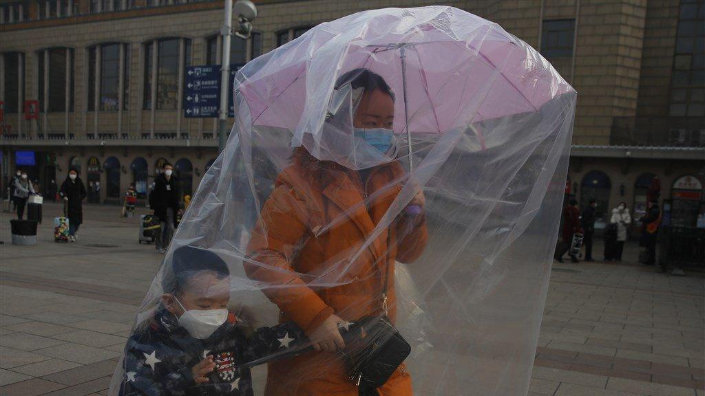 Een moeder en kind in Peking beschermen zich tegen het coronavirus.