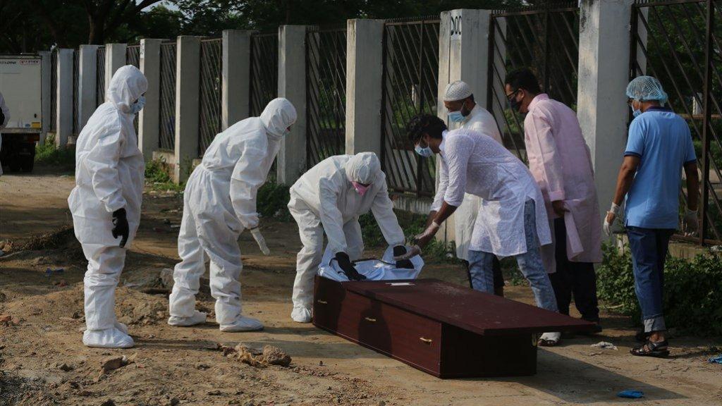 Een overleden coronapatiënt wordt begraven in Bangladesh.